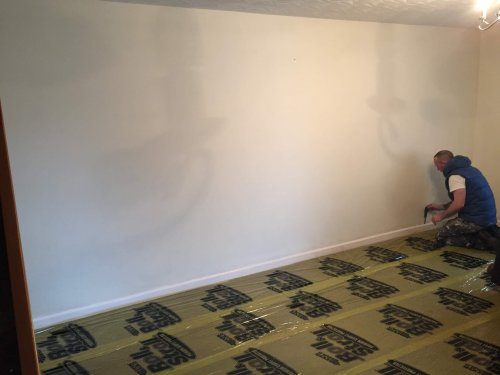 wall before with roll and stroll carpet protector on floor